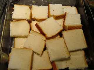 Slices of bread arranged in buttered baking dish.