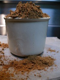 Measuring cup overflowing with natural cocoa powder.
