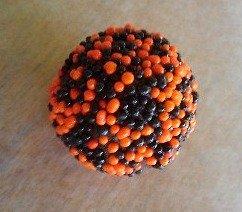 Halloween truffle covered in black and orange sprinkles.